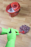 Cleaning floor. Cleaner is mopping wooden parquet floor Royalty Free Stock Images