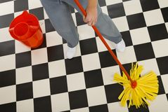 Cleaning floor. Woman standing with mop beside red bucket. Closeup on woman's legs and mop High angle view. White background royalty free stock images