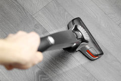 Cleaning floor with cordless vacuum cleaner Royalty Free Stock Photography