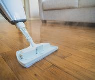 Steam cleaner. Cleaning the floor with a dry steam cleaner royalty free stock photography