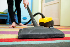 Cleaning floor with hoover Royalty Free Stock Image