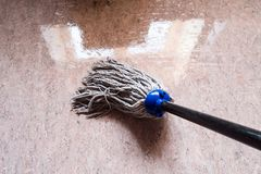 Cleaning floor linoleum by rope mop stock images