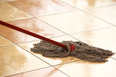 Cleaning the floor with a mop. Cleaning the floor with a old mop, mopping Stock Photo