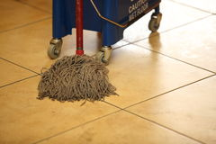 Cleaning the floor with a mop. Cleaning the floor with a old mop, mopping Stock Image