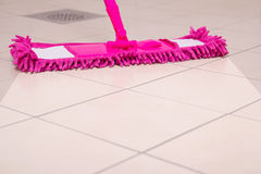 Cleaning the floor with pink mop Royalty Free Stock Images