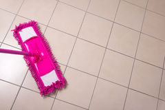 Cleaning the floor with purple mop Stock Image