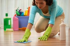 Cleaning floor. Young Asian housewife cleaning stain on wooden floor royalty free stock images