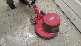 Cleaning of floors with red washing vacuum cleaner in factory. Sanitary treatment of industrial equipment. Chemical detergents stock footage