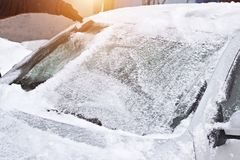 Cleaning frontal car glass from ice and snow, scraper, sun, auto. Cleaning frontal car glass from ice and snow, scraper, sun royalty free stock image
