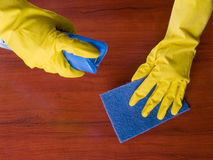 Cleaning furniture. Table in yellow gloves with blue sponge Stock Images