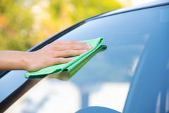 Cleaning glass car. Hand with green microfiber cloth, cleaning glass car Stock Images