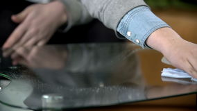 Cleaning the glass table with cloth and cleaning spray stock footage