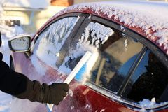 Brushing Snow off from the Glasses of a Red Car. Cleaning the glasses of a red car during winter. There is some snow on top of the car and a person is brushing royalty free stock photography