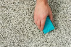 Cleaning gray carpet. With sponge above top view stock image