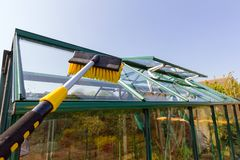 Cleaning a greenhouse roof with water fed pole. Telescopic water fed pole being used to clean the roof of a greenhouse stock images