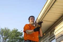 Cleaning Gutters On A Hot Day. Cleaning gutters of leaves on a hot day Royalty Free Stock Image