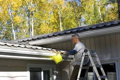 Cleaning the gutters of leaves Stock Photos