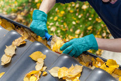 Cleaning gutters from leaves Stock Photos