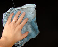 Cleaning hand. Hand cleaning a dark wood furniture Royalty Free Stock Image