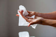 Cleaning hands and fingers with wet wipes. Young woman cleaning fingers and hands with wet wipes stock photos