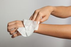 Cleaning hands with wet wipes. Young woman cleaning hands with wet wipes stock photo