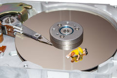 Cleaning the hard disk. A woman cleans a HDD. Figurine of a woman. Cleaners. Stock Images