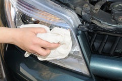 Cleaning headlights. Woman's hand with cotton rag cleaning SUV car's headlights royalty free stock photos