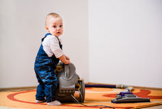 Cleaning home - baby with vacuum cleaner Stock Photo