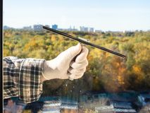 Cleaning a home window glass by squeegee. In sunny autumn day royalty free stock images