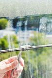 Cleaning of home window glass by squeegee. In sunny spring day Royalty Free Stock Image