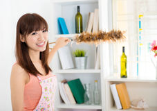 Cleaning house. Happy housewife cleaning house with duster royalty free stock image