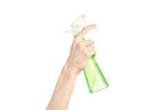 Cleaning the house and cleaner theme: man's hand holding a green spray bottle for cleaning isolated on a white background royalty free stock photos