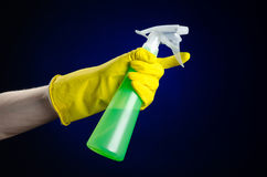 Cleaning the house and cleaner theme: man's hand in a yellow glove holding a green spray bottle for cleaning on a dark blue backgr Royalty Free Stock Photo
