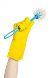 Cleaning the house and cleaning the toilet: human hand holding a blue toilet brush in yellow protective gloves isolated on a white Stock Images