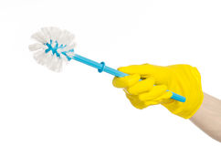 Cleaning the house and cleaning the toilet: human hand holding a blue toilet brush in yellow protective gloves isolated on a white Stock Photo