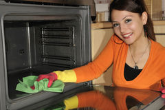 Cleaning the house - cooker. A casual girl using a disinfectant wipe to clean the cooker Stock Image
