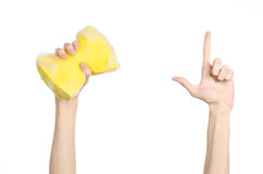 Cleaning the house and sanitation topic: Hand holding a yellow sponge wet with foam isolated on a white background in studio Royalty Free Stock Photos