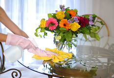 Cleaning house, spray and towel near flowers on table. House cleaning, woman washing table a color towel and detergent Stock Photos