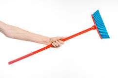 Cleaning the house topic: human hand holding a red broom. Isolated on a white background Stock Image