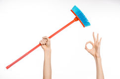 Cleaning the house topic: human hand holding a red broom Stock Photos