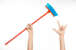 Cleaning the house topic: human hand holding a red broom. On a white background Stock Photos