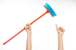 Cleaning the house topic: human hand holding a red broom. On a white background Royalty Free Stock Image