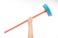 Cleaning the house topic: human hand holding a red broom Stock Photo
