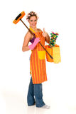Cleaning housewife. Attractive young housewife with curlers in hair and net on head, wearing colorful apron. Studio, white background Royalty Free Stock Images