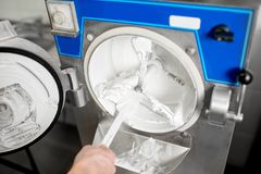 Cleaning ice cream maker machine. From the ice cream leavings Royalty Free Stock Photos