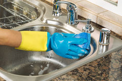 Cleaning inside of kitchen sink with soapy water and sponge. Closeup horizontal image of hand wearing rubber glove washing inside of kitchen sink with sponge and stock image