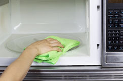 Cleaning inside of Microwave Oven stock photography