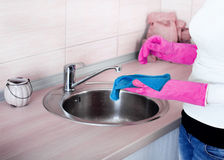 Cleaning kitchen sink and faucet Royalty Free Stock Image