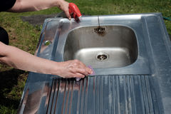 Cleaning Kitchen Sink. House wife hands with sponge cleaning a metal kitchen sink placed on the lawn, outdoor cropped shot stock photography