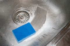 Cleaning kitchen sink. How to clean the stainless steel sink wit. H cleanser and washcloth. Blue sponge and scouring powder against the background of a metal royalty free stock photo